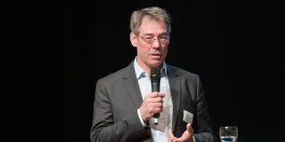 Ein Redner im grauen Anzug und weißem Hemd mit Mikrofon in der Hand am Rednerpult.