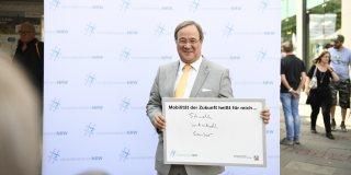 """Ministerpräsident Laschet hält ein ausgefülltes Schild in die Kamera: Mobilität heißt für mich... """"schnell, individuell, sauber"""""""