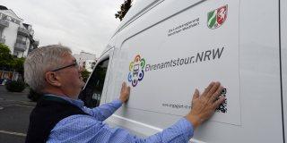 Ein älterer Herr beklebt den Ehrenamtstourbus seitlich mit dem Ehrenamtstour.NRW-Log