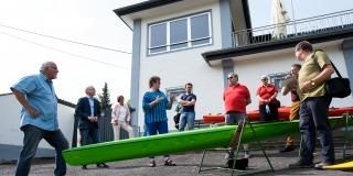Staatssekretärin Milz mit Vereinsmitgliedern vor dem Vereinshaus, vor Ihnen ein langes, grünes Kanu aufgebockt.