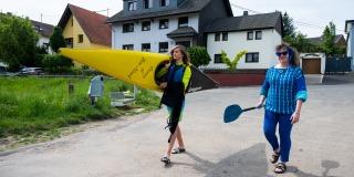 Staatssekretärin Milz mit einem Ruder ihrer rechten Hand geht neben einem jungen Mann, der ein gelbes Kanu trägt, eine Straße entlang.