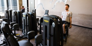 Zwei Trainierende sitzen auf fitnessgerten in einem Fitnessraum.