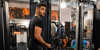 Ein junger Mann in schwarzen T-Shirt und Bermudahose mit weißen Socken und Sportschuhen geht durch einen Fitnessraum.