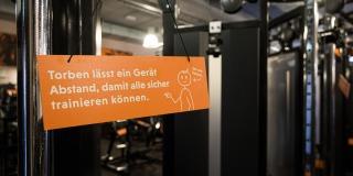 ein oranges Schild mit einem weißen Strichmännchen namens Torben und weißen Text dient alls Abstandshalter beim Training.