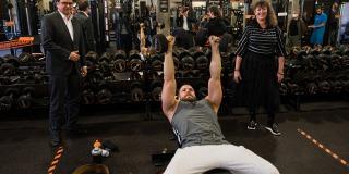 Ein Mann trainiert liegend auf einer Trainingsbank, Staatssekretärin Milz steht rechts daneben.