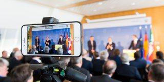 Pressekonferenz Olympiabewerbung aus der Sicht eines Smartphones.