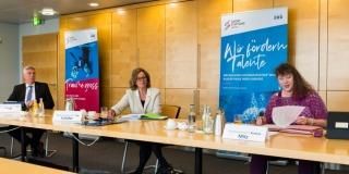Staatssekretärin Milz sitzt im weiten Abständen mit einer Dame und einem Herrn an einem langen Tisch.