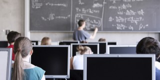 Auf dem Bild zu erkennen sind Schülerinnen und Schüler in einer Unterrichtsstunden am PC. Ein Lehrer schreibt Formeln an die Tafel.