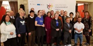 Staatssekretärin Andrea Milz steht rechts neben der Gruppe von Engagementpreisträgern.