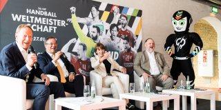 Ministerpräsident Laschet mit drei weiteren Personen in einer Gesprächsrunde zusammensitzend. Rechts im Hintergrund das schwarz-weiße Maskottchen.