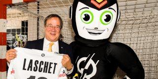 """Ministerpräsident Laschet steht mit Maskottchen im Handballtor, er hält ein weißes Handballer-T-Shirt mit seinem Namen """"Laschet"""" und der Nummer 19 ausgebreitet in seinen Händen."""