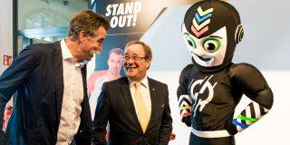 Ministerpräsident Laschet im Gespräch mit einem Mann, rechts neben ihm das Maskottchen.