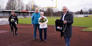 Frau Erika Rischko in weißer Daunenjacke und schwarzer Hose und Schuhen hält einen Blumenstrauß in ihren Händen. Neben ihr steht ein Herr in blauer Jacke. Links steh die Staatsekretärin Andrea Milz und ganz rechts der Bürgermeister von Langenfeld.