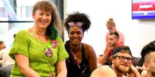 Staatssekretärin Andrea Milz sitzt mit jungen Sportlern zusammen, direkt neben ihr sitzt eine afrikanisch aussehende Frau.