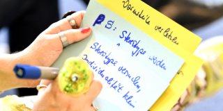 Staatssekretärin Andrea Milz schreibt mit blauer Tinte auf einemn weißen Blatt.