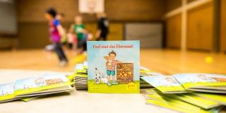 Ein Pixi Buch steht aufgestellt auf einem Tisch. Im Hintergrund sieht man Kinder,die in einer Sporthalle spielen.