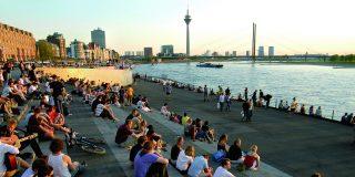 Sitzende Menschen auf Treppe am Rhein