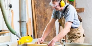 Das Bild zeigt einen Handwerker an einer industriellen Holzschneidemaschine.