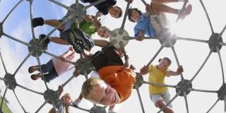 Auf dem Foto sind Kinder auf einem Klettergerüst auf einem Spielplatz abgebildet.