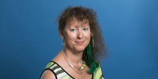 Staatssekretärin Andrea Milz freundlich lächelnd - Hintergrund blau.