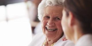 Das Bild zeigt eine lächelnde alte Frau im Gespräch mit einer anderen Person.