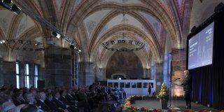 Bundespräsident Steinmeier hält eine Rede auf einer Bühne mit Rednerpult stehend.