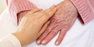 Bild auf dem eine Pflegerin die Hände einer älteren Frau streichelt