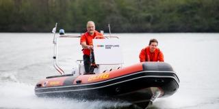 Zwei Männer fahren auf einem Schlauchboot des DLGR über Wasser