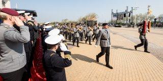 Militärparade von grau-schwarz uniformierten Soldaten.