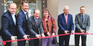 Staatssekretärin Andrea Milz und andere beim Durchschneiden des roten Einweihungsbandes des neuen Funktionsgebäudes der Bobbahn.