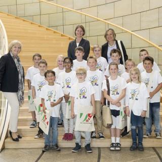 Ministerpräsidentin Hannelore Kraft und Schulklasse stehen auf einer Trepper im Landtag