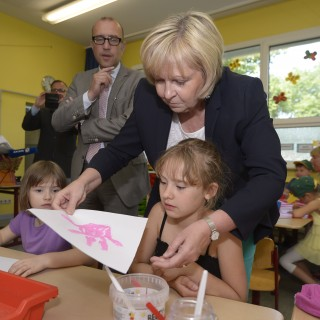 Ministerpräsidentin Hannelore Kraft bastelt mit Kindern am Tisch