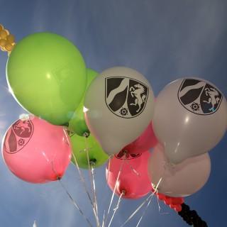 Das Bild zeigt bunte Luftballons mit NRW-Wappen.
