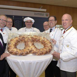 Ministerpräsident Armin Laschet und eine Gruppe von Bäckern stehen an einem Tisch mit einer großen Brezel