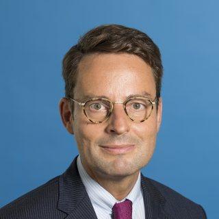 Staatssekretär Bothe freundlich lächelnd - Hintergrund blau.