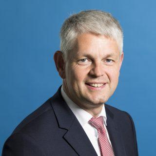 Staatssekretär Dammermann freundlich lächelnd - Hintergrund blau.