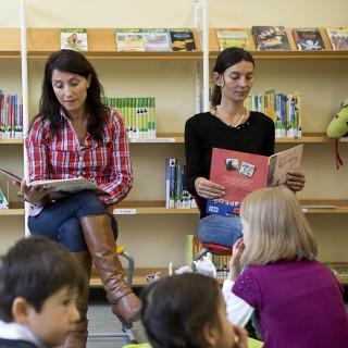 Das Foto zeigt, wie Necmiye Immig als Lesepatin eine Geschichte auf Türkisch vorliest. Eine zweite Mutter liest die Geschichte auf Deutsch vor.