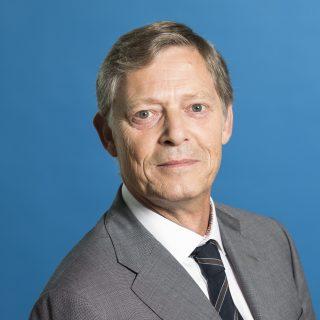 Staatssekretär Heller freundlich lächelnd - Hintergrund blau.