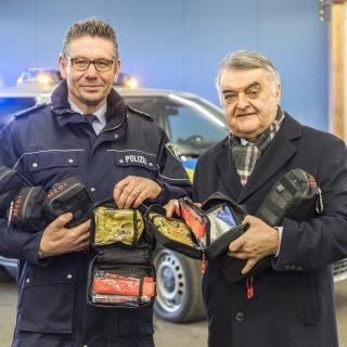 Minister Reul überreicht Medipacks an Dietmar Henning von der Polizei Düsseldorf. Im Hintergurnd steht ein Polizeiwagen.