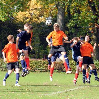 Studenten mit orangen und dunkelblauen Trikots beim Fussbalspielen. Ein Fussballspieler mit orangen Trikot springt hoch und setzt zum Kopfball an.