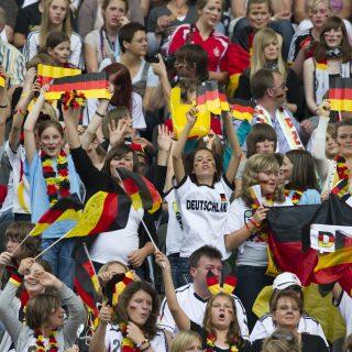 Fussballfans stehend auf der Tribüne mit Deutschland-Flaggen.
