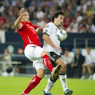 2 Fußballspieler im Zweikampf um den Ball, im Hintergrund eine vollbesetzte Tribüne.