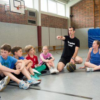 Sportlehrer sitzt mit einigen Schülern im Halbkreis auf den Boden eienr Turnhalle.