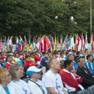 Viele Menschen in Sportkleidung lauschen sitzend einer Rede, im Hintergrund sind viele Flaggen.