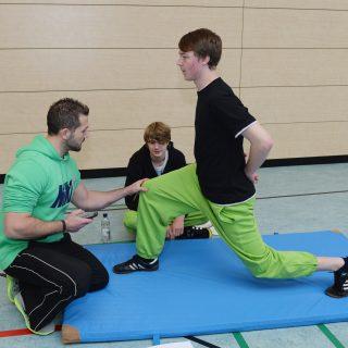 Ein Schüler steht mit angewinkelten Knien im tiegen Stand auf einer bleuen Trunmatte. Ein Sportlehrer prüft den Stand eines Schülers. Im Hintergrund sitzt noch ein Schüler auf den Boden der Turnhalle.
