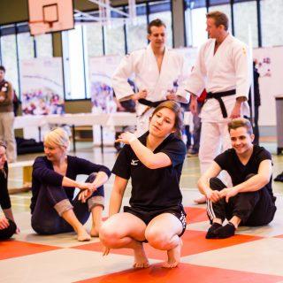 Mehrere Frauen bei Dehnübungen für einen Selbstverteidungskurs in einer Turnhalle. Auf dem Boden grüne und rote Matten im Schachbrettmuster. Im Hintergrund zwei Kampfsportler in weißen Anzügen mit schwarzen Gürteln.