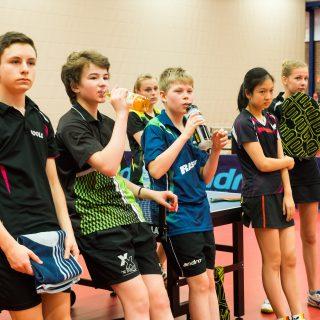 Jugendliche Tischtennisspielerinnen und -spieler, die sich an einer Tischtennisplattte ausruhen.