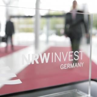 Das Bild zeigt das Logo von NRW.INVEST auf einer Tür.