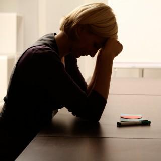 Das Foto zeigt eine Person, die alle an einem Besprechungstisch sitzt und unter Stress leidet.