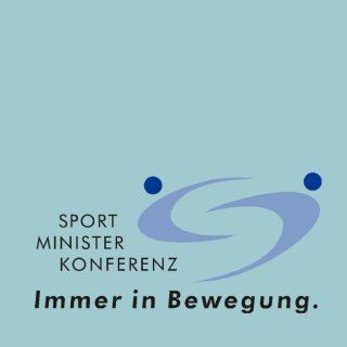 """Ein """"S"""" in einem speziellen Design-Logo oben mit 2 blauen Punkten links und rechts. Rechts daneben steht """"Sport Minister Kompetenz"""", unter dem Text und dem Logo steht """"Immer in Bewegung"""". Der Hintergurnd ist in hellblau gehalten."""
